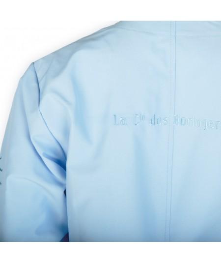 """Blouse d'horloger Latitude La Cie Des Horlogers, de couleur bleu clair. Écriture """"La Cie des Horlogers"""" au dos."""